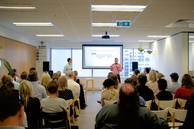Image of Portable cofounders Andrew Apostola and Simon Goodrich presenting in front of a large seated crowd of people